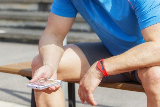 Sportler mit Fitness-Tracker und Smartphone