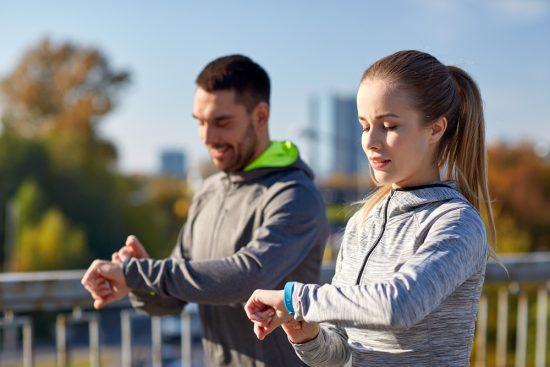 Zwei Jogger kontrollieren die Werte der Fitness-Armbänder.